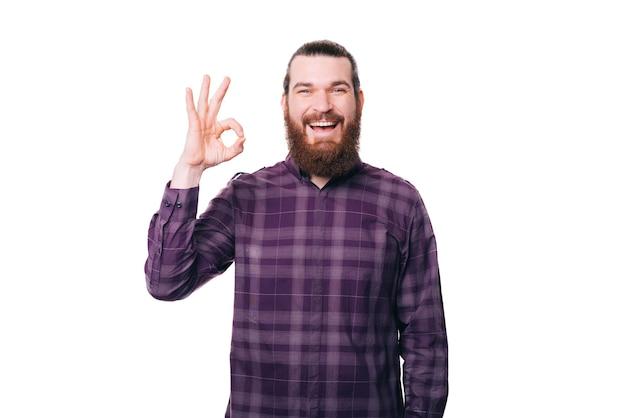 Фотография улыбающегося веселого бородатого мужчины, показывающего жест ок