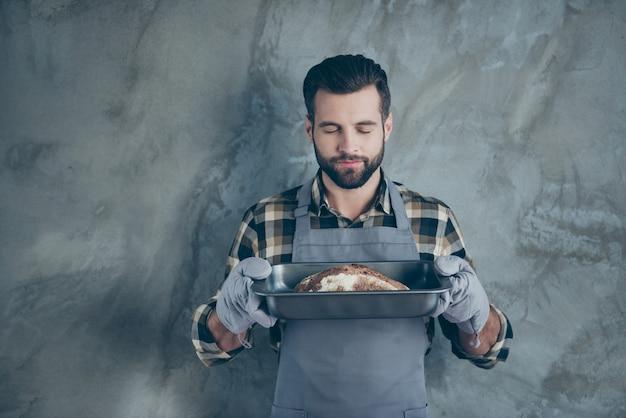 Фотография улыбающегося жизнерадостного и позитивного красивого повара, испекшего хлеб и нюхающего его фантастический аромат на подносе, изолировала стену серого цвета бетонную стену