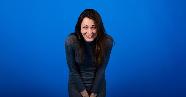 파란색 배경에 회색 드레스를 입고 웃고 있는 쾌활한 젊은 여성의 사진. 감성적인 초상화