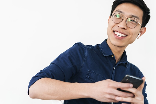 白い壁に隔離されたオフィスで働いている間椅子に座って携帯電話を保持しているイヤポッドを身に着けている笑顔の中国人ビジネスマンの写真
