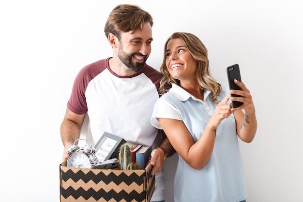 白い壁に隔離された携帯電話を使用しながら段ボール箱を保持しているカジュアルな服を着て笑顔のカップルの写真
