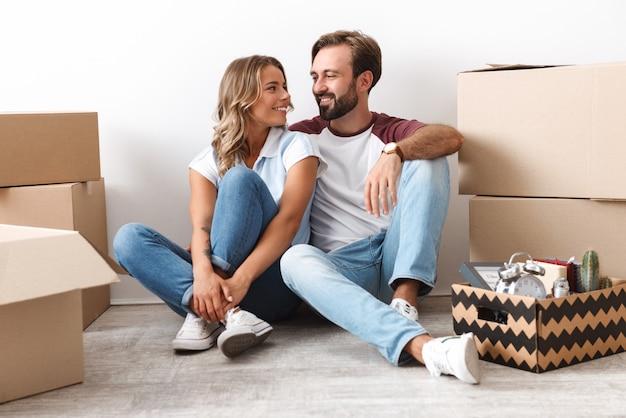 白い壁に隔離された段ボール箱の近くに座って抱き締めてカジュアルな服を着て笑顔のカップルの写真