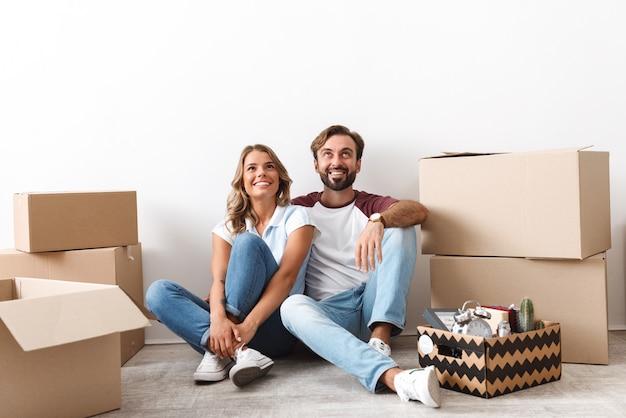 白い壁に隔離された段ボール箱の近くに座って上向きに見ているカジュアルな服を着て笑顔のカップルの写真