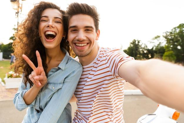도시 공원에서 오토바이에 함께 앉아있는 동안 휴대 전화에 셀카를 복용 웃는 커플의 사진