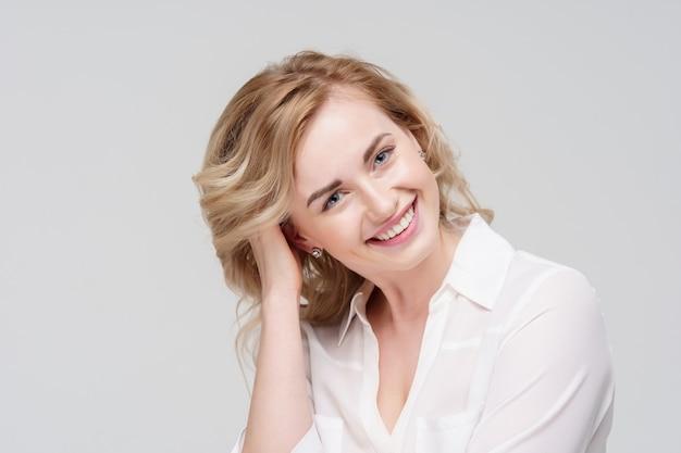 スタジオで白いシャツを着て笑顔の巻き毛の女性の写真