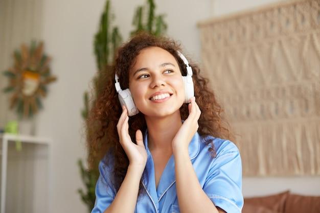 笑顔の巻き毛の若い素敵なアフリカ系アメリカ人の女性の写真、広く笑顔、ヘッドフォンでお気に入りの音楽を聴き、ヘッドフォンを保持し、日曜日の朝を楽しんで、幸せな表情で目をそらします。