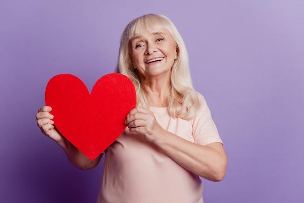 Фотография улыбающейся пожилой женщины держит большую валентинку в форме сердца, изолированную на фиолетовом фоне