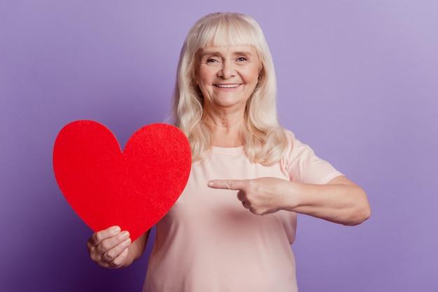 Фотография улыбающейся пожилой женщины указывает пальцем на большую валентинку в форме сердца, изолированную на фиолетовом фоне