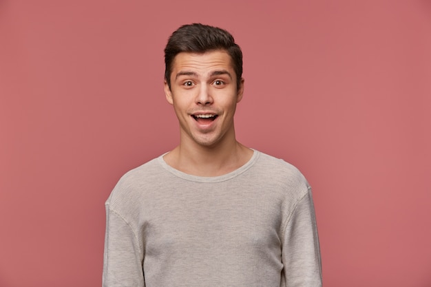 Фотография улыбающегося красивого молодого парня носит пустой длинный рукав, смотрит в камеру с счастливым выражением лица, стоит на розовом фоне.