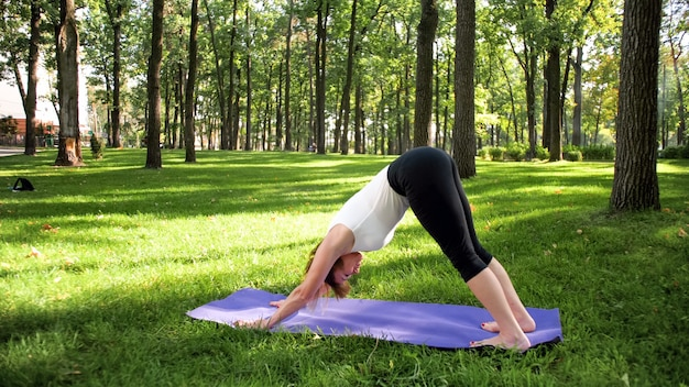 Фотография улыбающейся счастливой женщины 40 лет, делающей упражнения йоги на фитнес-коврике в лесу. гармония человека в природе. люди среднего возраста, пользующиеся автомобилем психического и физического здоровья