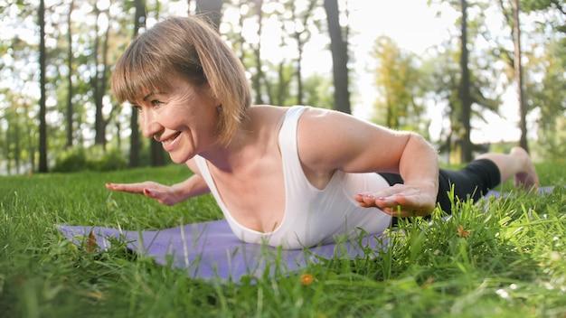 森のフィットネスマットでヨガの練習をしている40歳の笑顔の幸せな女性の写真。自然界の人間の調和。心身の健康を車で運ぶ中年
