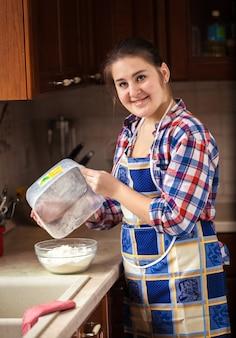 ボウルから小麦粉を散りばめている笑顔の主婦の写真