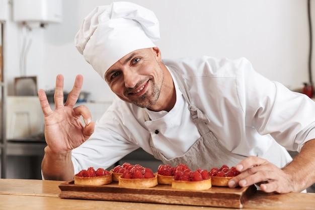 케이크와 함께 접시를 들고 흰색 제복을 입은 웃는 남성 최고 사진