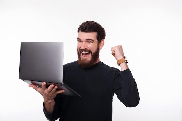 Фотография улыбающегося человека праздновать победу и проведение ноутбук на белом фоне