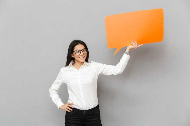 テキストの空のcopyspaceバブルを保持し、灰色の背景に分離されたカメラを探しているビジネスライクな服を着て笑顔のオフィスの女性の写真