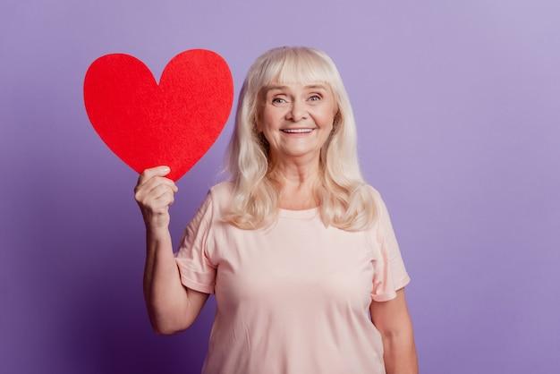 Фотография улыбающейся старой красивой женщины держит большое красное сердце карты, изолированное на фиолетовом фоне