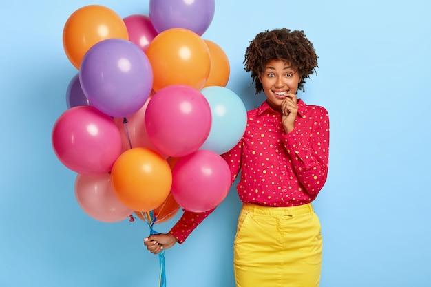 웃는 기쁘게 여자의 사진 포즈를 취하는 동안 여러 가지 빛깔의 풍선을 보유