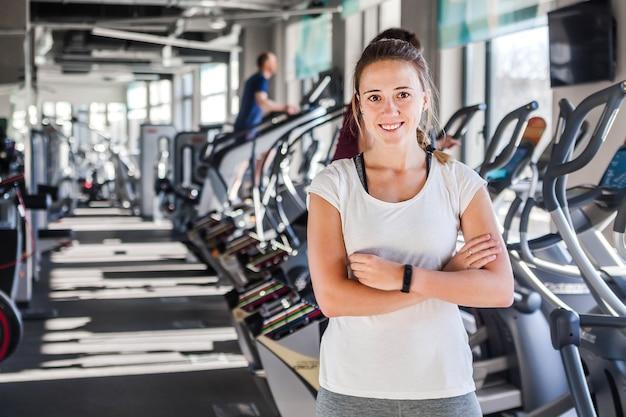 Фотография улыбающейся спортивной кавказской женщины, стоящей с крестом оружия и смотрящей в камеру на фоне фитнес-зала с копией пространства в левой части. концепция тренера или инструктора по фитнесу.