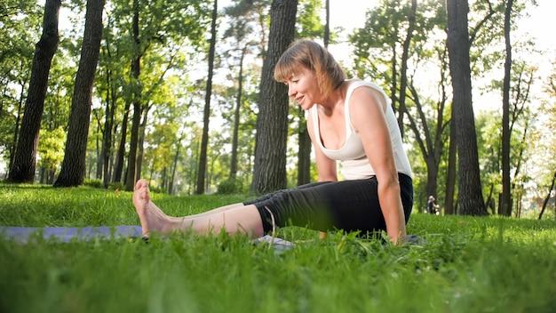 ヨガやフィットネスのエクササイズをしている笑顔の女性の写真。健康管理をしている中年。自然の中での心と体の調和