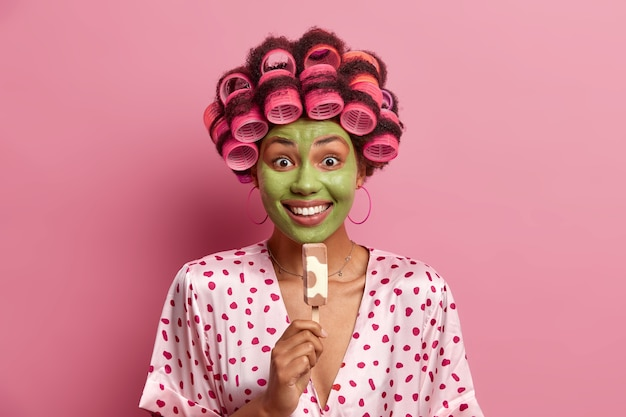 笑顔の女性の写真は広く笑顔で、緑の保湿マスクを適用し、スティックにおいしいアイスクリームを食べ、ヘアカーラー、シルクのガウンを着て、夏の時間を楽しんでいます。冷菓の主婦