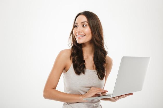 흰 벽 위에 절연 은색 개인용 컴퓨터에서 작업하는 동안 멀리보고 긴 갈색 머리를 가진 웃는 여자의 사진