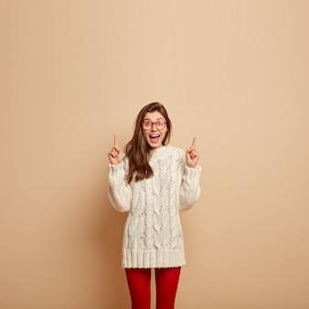 만족스러운 표정으로 웃는 여자의 사진, 행복하게 웃고, 위의 것을 보여주고, 위쪽을 가리키고, 광고 콘텐츠를위한 공간을 보여주고, 니트 흰색 스웨터를 입고, 투명 안경을 착용합니다.