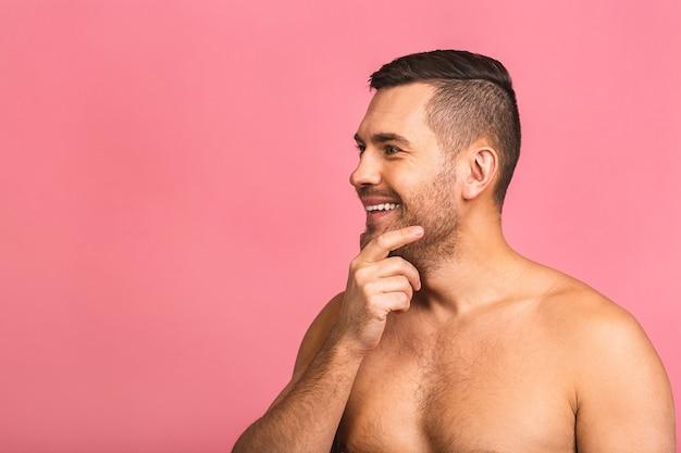 Фотография улыбающегося молодого красивого человека, стоящего голым. концепция ухода за кожей человек в ванной комнате.