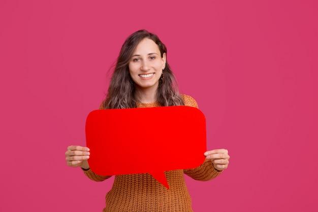 Фото улыбающегося молодая женщина, держащая красный речи пузырь