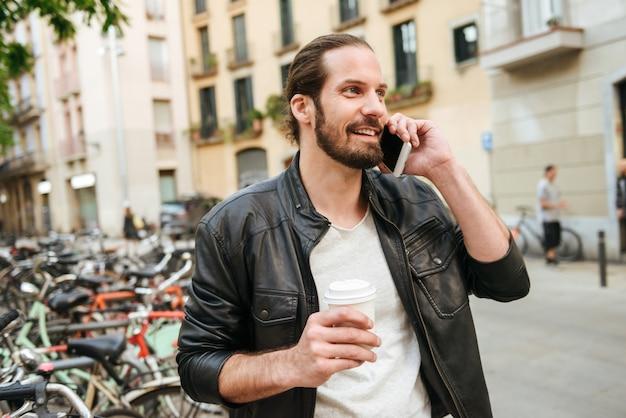 テイクアウトのコーヒーを保持しているカジュアルな服を着て、笑顔で携帯電話で話している30代の社交的な魅力的な男性の写真