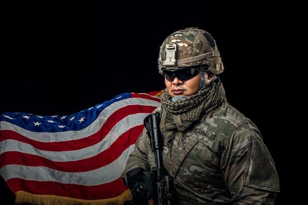 背景に米国旗を保持している兵士の写真。ライフルを保持している特殊部隊の米国の兵士または軍事請負業者。背景の画像。兵士、軍隊、戦争、武器、技術の概念。