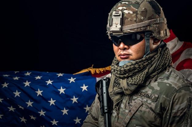 백그라운드에서 미국 국기를 들고 군인의 사진. 특수 부대 미국 군인 또는 소총을 들고 군사 계약자. 배경 이미지입니다. 군인, 군대, 전쟁, 무기 및 기술 개념.