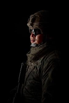 黒の背景の兵士の写真。特殊部隊の米国の兵士またはライフルを保持している民間軍事請負業者。黒の背景の画像。兵士、軍隊、戦争、武器、技術の概念。
