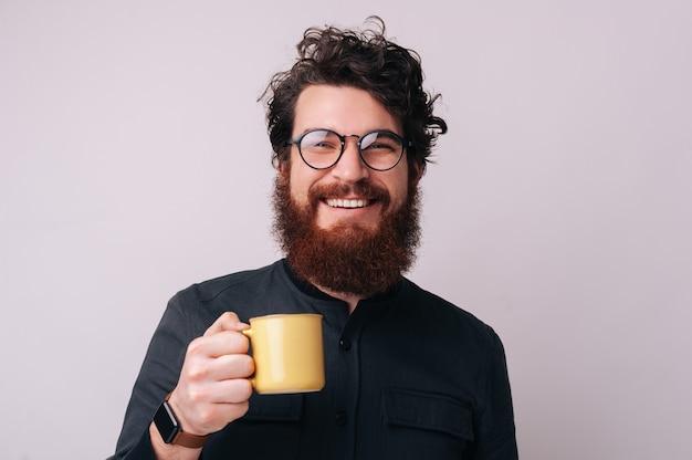 孤立した背景の上に、眼鏡をかけ、カメラを見て、コーヒーとマグカップを保持しているいくつかの陽気なひげを生やした男の写真