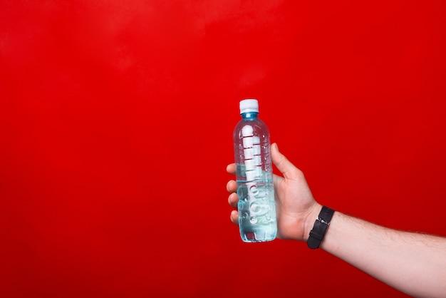 빨간 벽 근처에 물병을 들고 누군가의 사진