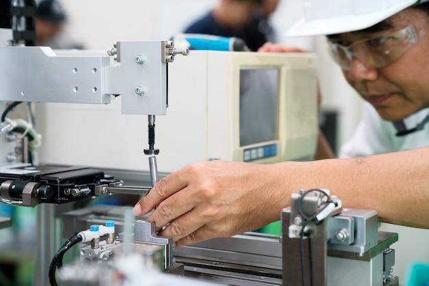 공장에서 생산 기계의 전문 남성 엔지니어 측정 부품의 사진.