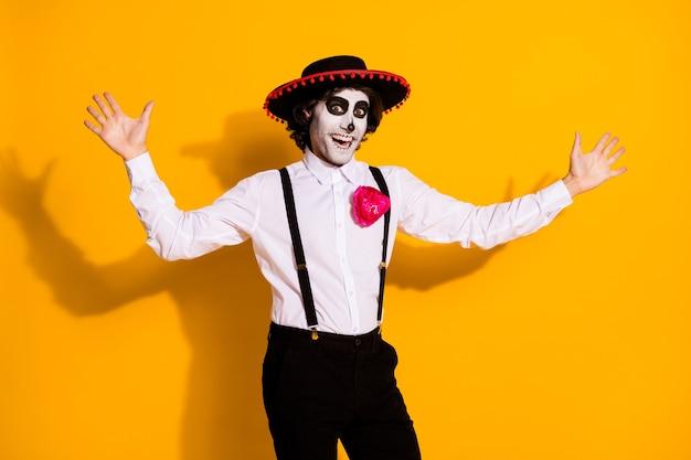 으스스한 펑키 남자 미친 시도 점프 겁의 사진이 아무데도 나타나지 않아 모두가 카니발을 입고 흰색 셔츠 장미 죽음 의상 솜브레로 멜빵 고립 된 노란색 배경