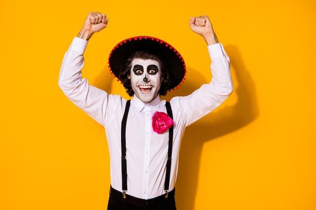 으스스한 괴물 남자의 사진은 거대한 상금 축제 테마 이벤트 경쟁에서 우승한 손을 주먹으로 들고 흰색 셔츠 죽음 의상 설탕 두개골 멜빵 격리된 노란색 배경을 착용합니다.