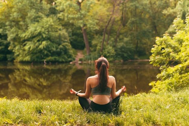 朝の間に湖の近くで瞑想しているスポーツの女性の写真