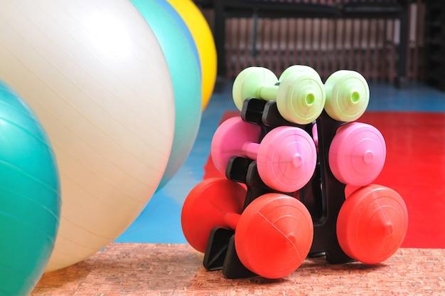 ジム用のスポーツ用品、ヨガとシェーピング、さまざまな色のダンベルとフィットネスボールの写真