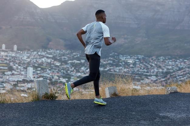 カジュアルなtシャツ、黒のレギンス、トレーナーを着たスポーツマンの写真は、山道をすばやく走り、速いジョギングをし、田舎の素敵な風景に立ち向かい、自己決定的で強い