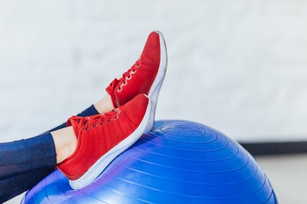 Фотография спортивных красных кроссовок на синем фитнес-мяче.