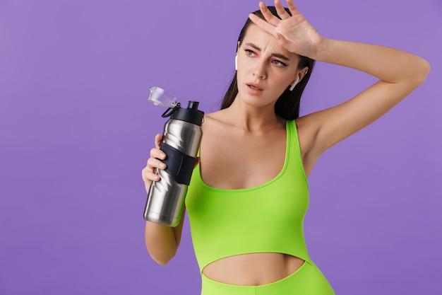 イヤポッドを使用し、水筒を保持している明るいメイクでスポーティな疲れた女性の写真
