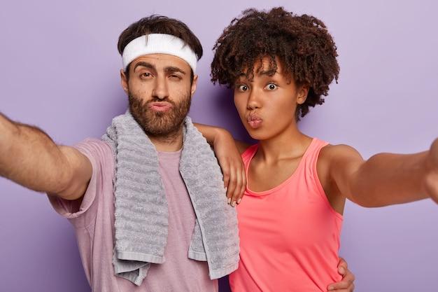 スポーティな女性と男性の写真は手を伸ばし、自分撮りの肖像画を作り、唇を折りたたんで、アクティブな服を着て、肩に柔らかいタオルをかけます