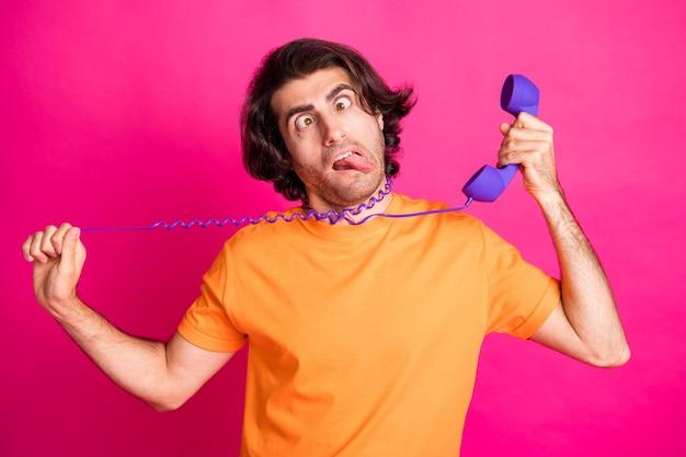Фотография косоглазого человека с языком держать телефон удушающий провод носить оранжевую футболку изолированный розовый цвет фона