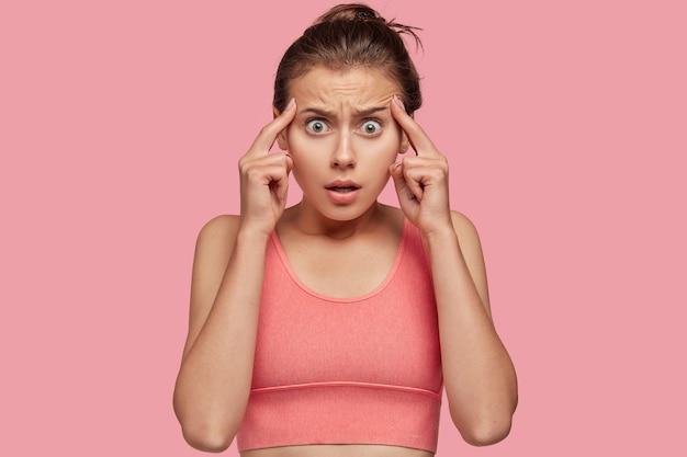 На фото переутомленная молодая спортсменка держит оба указательных пальца на висках