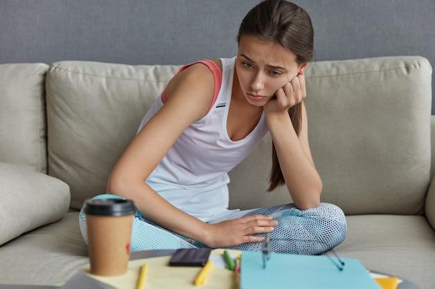 ストレスを感じている動揺した女子高生の写真は、疲れを感じ、必死に見下ろし、紙とペンでデスクトップに座っています。