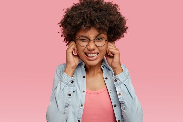 스트레스가 많은 불쾌한 흑인 여성의 사진에는 아프로 헤어 스타일이 있습니다.