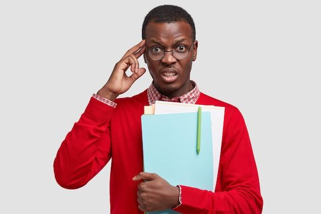 Фото стрессового, недовольного темнокожего молодого парня, держащего руку на виске, хмурого лица, одетого в элегантный красный свитер