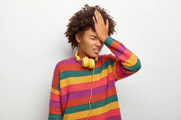ストレスの多い民族女性の写真は、手のひらで額を叩き、重要な情報を忘れたり、間違ったことを後悔したり、色とりどりのジャンパー、ヘッドフォンを着用したりします