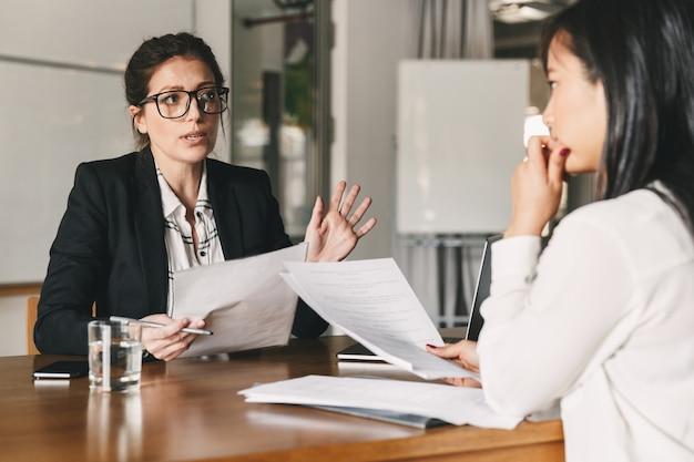 Фотография строгой кавказской женщины, держащей резюме и ведущей переговоры с кандидатом-женщиной во время корпоративной встречи или собеседования - концепция бизнеса, карьеры и трудоустройства